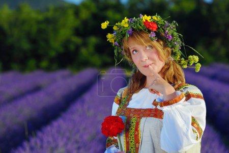 Photo pour Fille paysanne rêveuse dans une couronne de fleurs vêtue d'une robe russe se tient dans le champ de lavande - image libre de droit