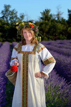 Photo pour Fille paysanne dans une couronne de fleurs vêtue d'une robe russe se tient dans le champ de lavande - image libre de droit