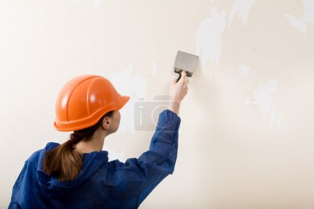 Woman worker removes old wallpaper...