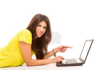 Photo pour Jeune femme présentant votre produit sur un ordinateur portable - image libre de droit