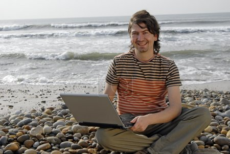 Young man at the beach with laptop
