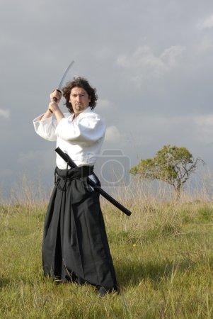 Photo pour Jeune homme aikido avec une épée, extérieur - image libre de droit