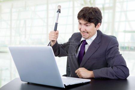 Photo pour Jeune homme d'affaires fou avec un marteau fracassant un ordinateur portable - image libre de droit