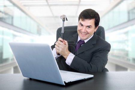 Photo pour Homme d'affaires heureux avec un marteau fracassant un ordinateur portable, au bureau - image libre de droit