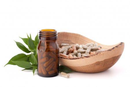 Herbal drug capsules in brown glass bottle isolate...