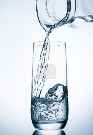 Pouring water from glass pitcher
