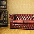 Old Red Genuine Leather Sofa Near The Fireplace...