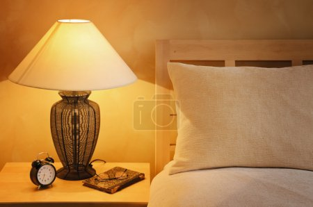 Photo for Close Up Fragment Of The Bedroom With Reading Lamp And Alarm Clock - Royalty Free Image
