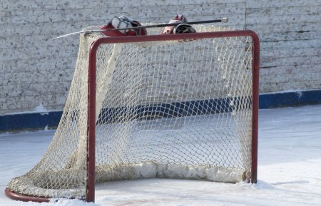 Photo for Hockey gate with gloves and stick on it. Winter sport game - Royalty Free Image