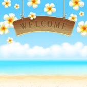 Wooden signboard Welcome hangs against tropical flowers and sea shore