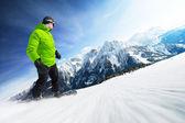 Snowboardista na sjezdovce ve vysokých horách