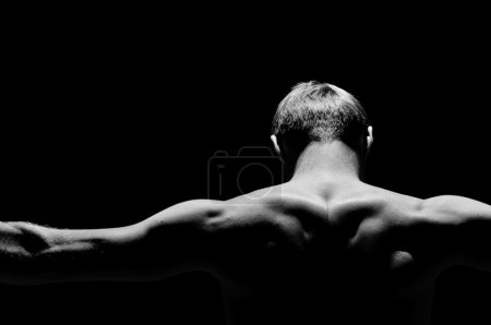Photo for Back of the strong man on a black background - Royalty Free Image