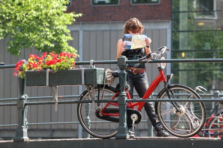 Tourist with map and bicycle. Amsterdam, Netherlands.
