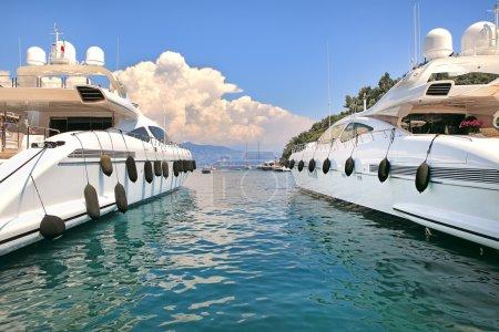 Two white luxury yachts on Mediterranean sea.