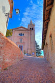 Old church and narrow street. Monticello DAlba, Italy.