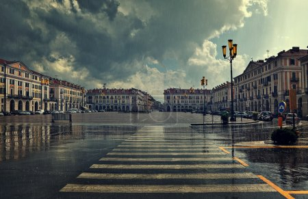 Photo for Pedestrian crossing and big plaza at city center under cloudy sky at rainy day in Cuneo, Italy. - Royalty Free Image