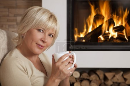 Photo for Adult woman enjoying winter hot drink near home fireplac - Royalty Free Image