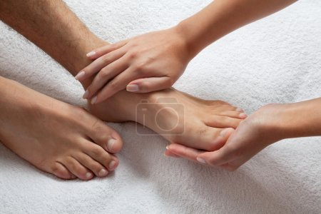Photo for Close up of female masseuse giving a foot massage to man - Royalty Free Image