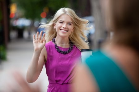 Photo for Happy shopping woman greeting friend on street - Royalty Free Image