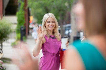 Photo pour Heureuse jeune femme avec tasse de café jetable saluant un ami féminin - image libre de droit