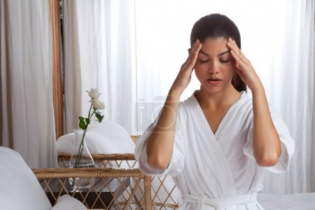 Photo for Young woman massaging her face wearing bathrobe. - Royalty Free Image