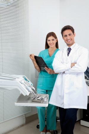 Photo for Portrait of young male dentist and assistant standing in dental clinic - Royalty Free Image