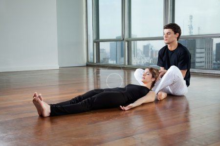 Instructor helping Woman In Yoga Exercise