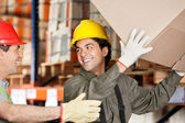Foreman With Coworker Lifting Cardboard Box At Warehouse