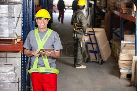 Photo pour Portrait de contremaître heureux mi-adulte avec tablette numérique et collègue poussant camion à main à l'entrepôt - image libre de droit