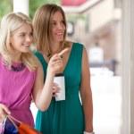 Two happy window shopping women looking at merchan...