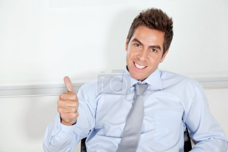 Photo pour Portrait de pouces gesticulant de beau jeune homme d'affaires vers le haut au bureau - image libre de droit