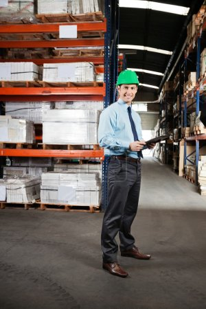 Confident Supervisor With Clipboard At Warehouse
