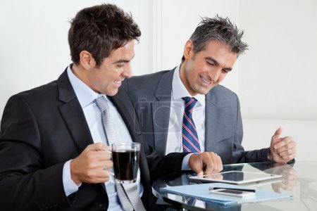 Photo for Two happy businessmen using digital tablet at desk in office - Royalty Free Image