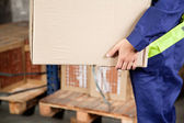 Foreman Carrying Cardboard Box At Warehouse