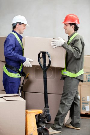 Photo pour Deux contremaîtres, boîte en carton de levage à entrepôt - image libre de droit