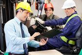 Mužské vedoucí komunikace s řidič vysokozdvižného vozíku a foreman