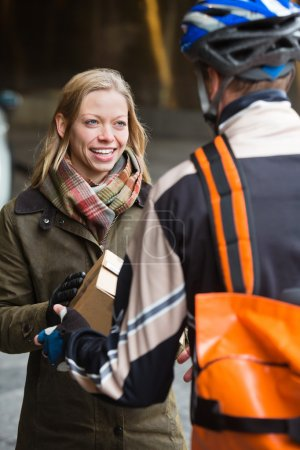 Smiling Young Woman Receiving A Package From Courier Delivery Ma
