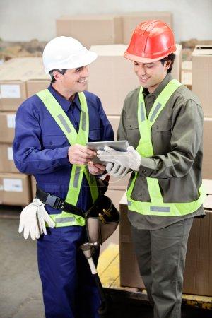 Photo pour Heureux jeunes contremaîtres en utilisant la tablette numérique dans l'entrepôt - image libre de droit