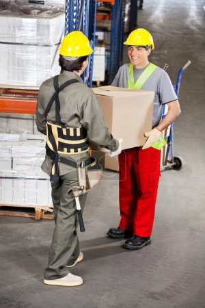 Foremen Carrying Cardboard Box At Warehouse