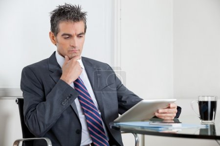 Contemplative Businessman Using Digital Tablet In Office
