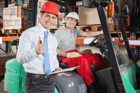 Photo for Portrait of supervisor gesturing thumbs up with forklift driver sitting behind - Royalty Free Image