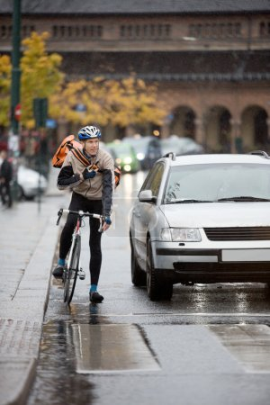 Male Cyclist With Backpack Using Walkie-Talkie On Street