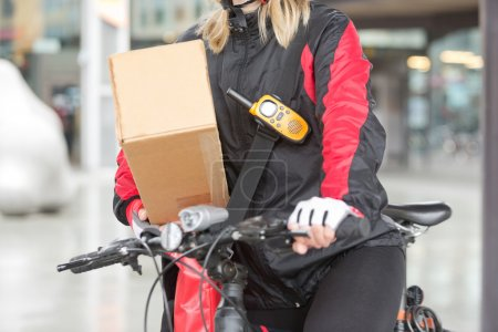 Female Cyclist With Cardboard Box And Courier Bag On Street