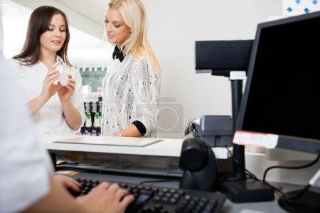 Sales Clerk Assisting Woman In Pharmacy