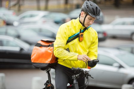 Male Cyclist With Courier Bag Using Mobile Phone On Street