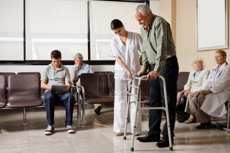 Photo pour Homme âgé aidé par une infirmière pour marcher dans le cadre Zimmer avec assis dans le hall de l'hôpital - image libre de droit