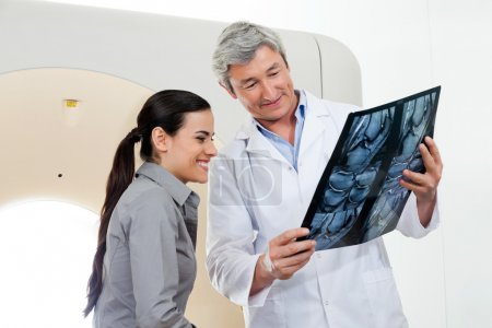 Radiologist Showing X-ray Report To Patient