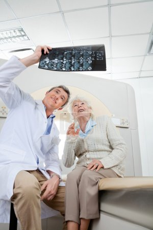 Radiologist With Patient Looking At X-ray