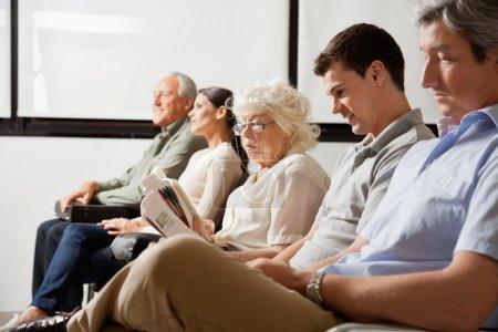 Photo pour Rangée d'attente multiethnique pour le médecin dans le hall de l'hôpital - image libre de droit
