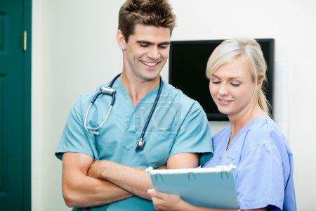 Photo pour Jeune infirmière montrant presse-papiers à sourire vétérinaire masculin à la clinique - image libre de droit